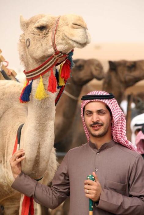 Un hombre de Kuwait posa con su camello en una pre competencia en el dis...