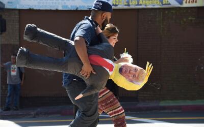 Dos inmigrantes caminan por una calle de Chicago llevando una piñata con...