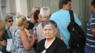 Un grupo de clientes aguarda en las afueras de un banco en Atenas para p...