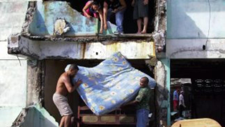 Unas personas recogen sus pertenencias de las casas destruidas por el pa...