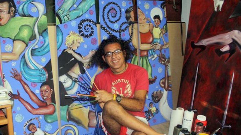 El artista plástico Alonso Rey-Sánchez posa con su pieza desplegada hoy...