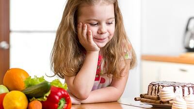 A child making a decision between healthy food and sweets.