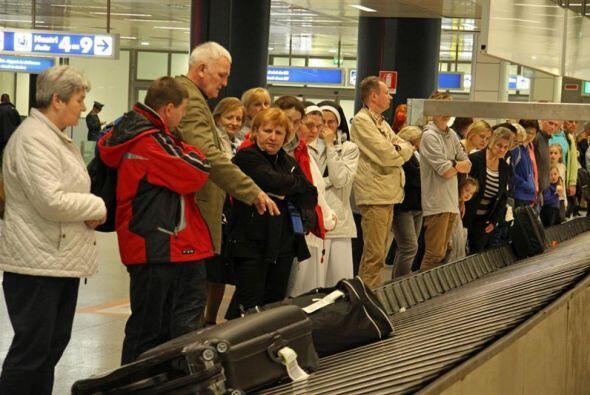 Un grupo de peregrinos polacos espera para recoger su equipaje en el aer...