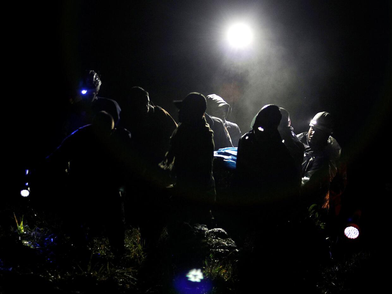 Trabajadores de rescate transportan el cuerpo de una víctima del acciden...