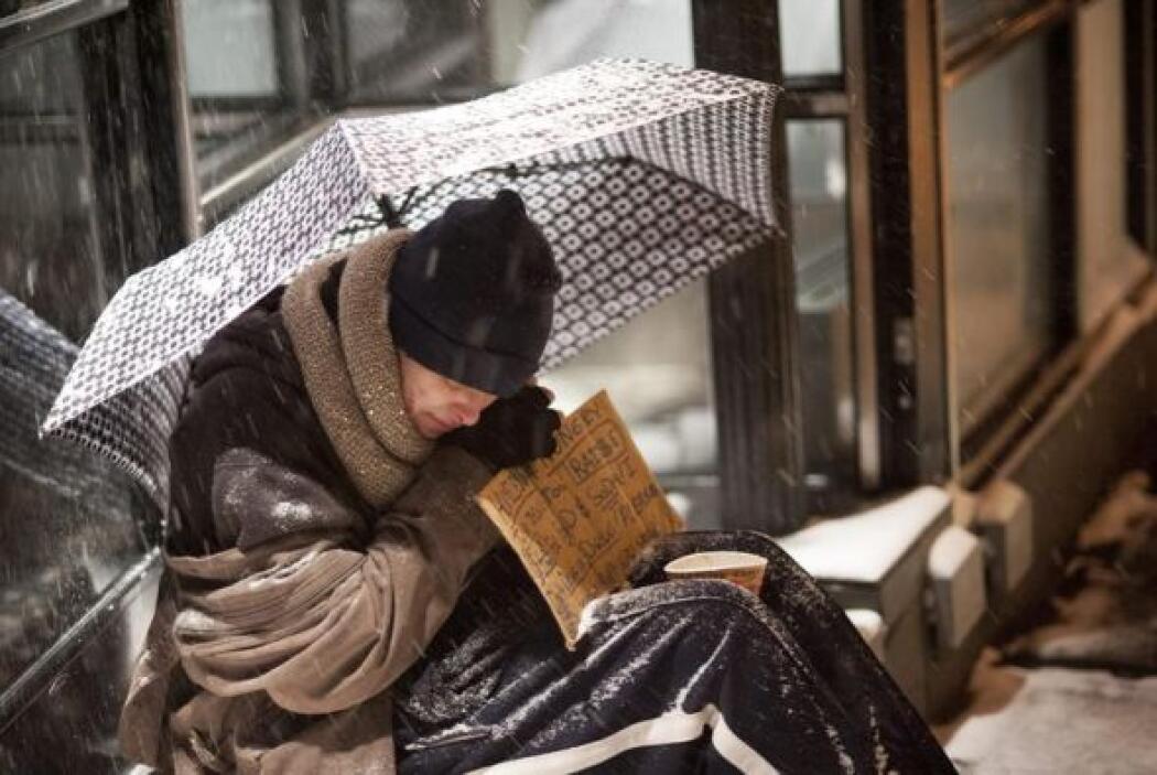Un sin techo se cubre con un paraguas durante una nevada en Nueva York.