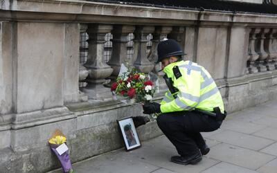 Un policía coloca una ofrenda en recuerdo de su compañero...