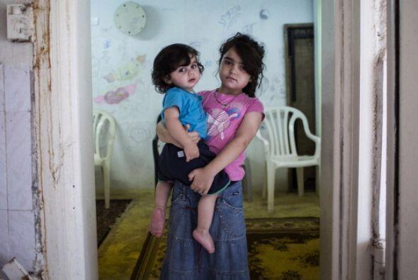 Niños   posan para   una fotografía   mientras juegan en un   refugio co...