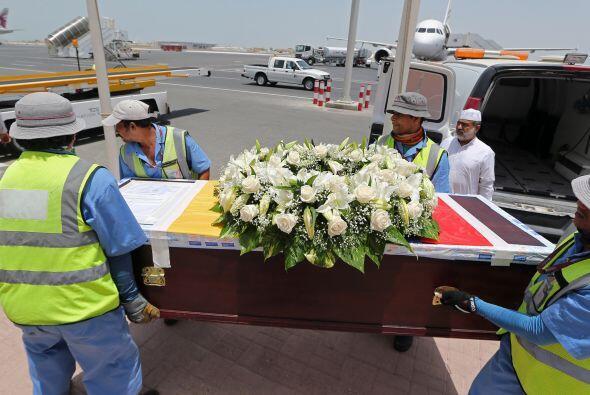 El ataúd, cubierto con flores y una enorme foto del futbolista de...