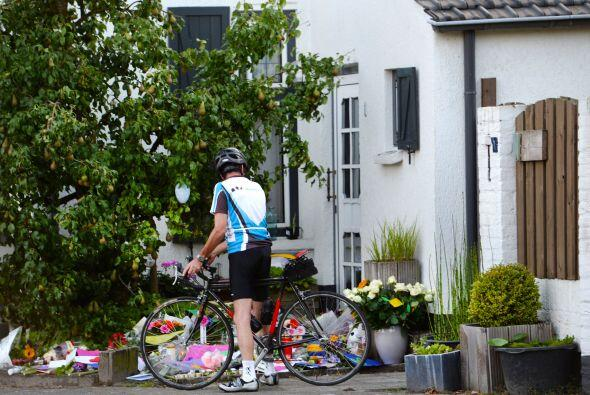 Un ciclista mira varios ramos de flores afuera de la casa de una familia...