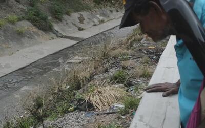 En las aguas negras de un río de Venezuela, desamparados buscan objetos...