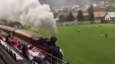 Un tren pasa junto a un campo de fútbol en Eslovaquia.