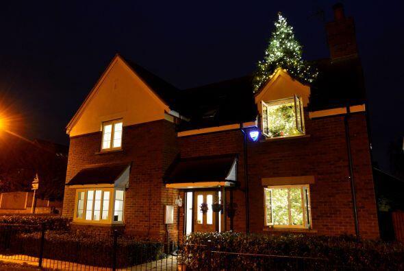 Este árbol de navidad gigante que atraviesa el techo de una casa se encu...
