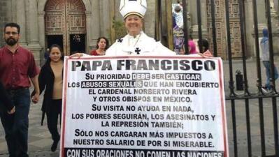 Una persona protesta por la visita del papa a México