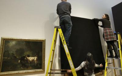 Operarios del museo tapan obras realizadas por inmigrantes.