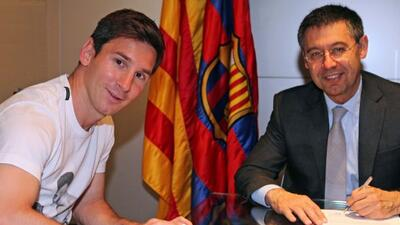 Messi posa junto al presidente Bartomeu durante la firma de su mejora de...