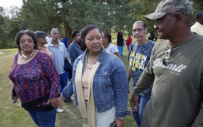 Stacey Payton, madre de la víctima, al centro de la foto, y a la...