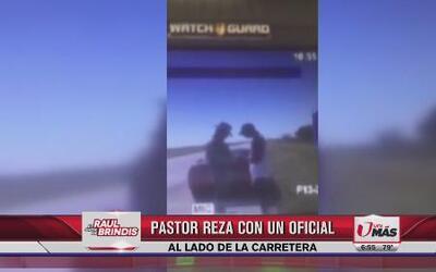 Pastor reza con oficial al lado de la carretera