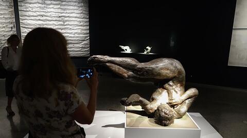 Una mujer retrata la escultura 'Tumbling Woman' (2002) del artista Eric...