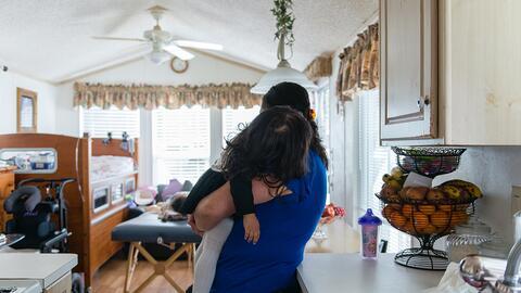 Sonia sostiene a su hija menor, Camila, mientras un terapeuta le aplica...