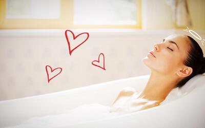 Mujer relajada en tina tomando baño con burbujas