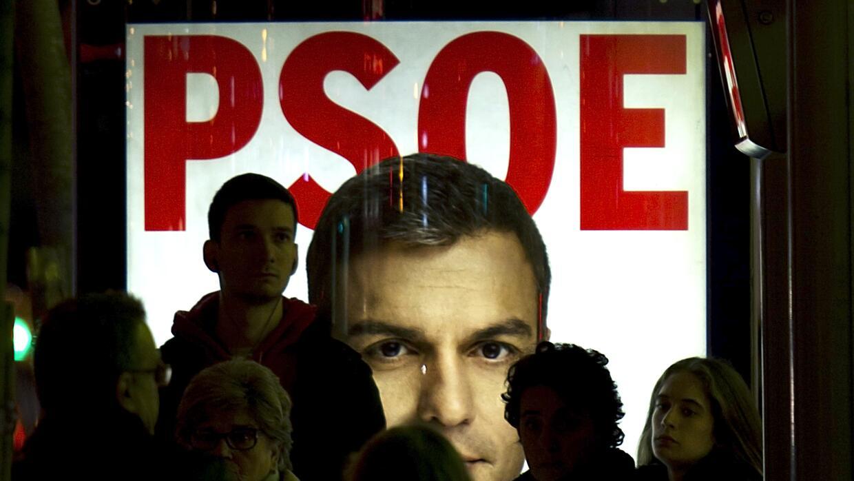 Varias personas delante de un cartel de Pedro  Sánchez.