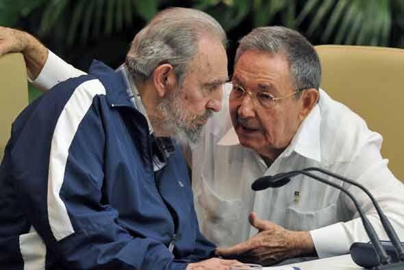 El expresidente cubano Fidel Castro escucha con atención a su hermano Ra...