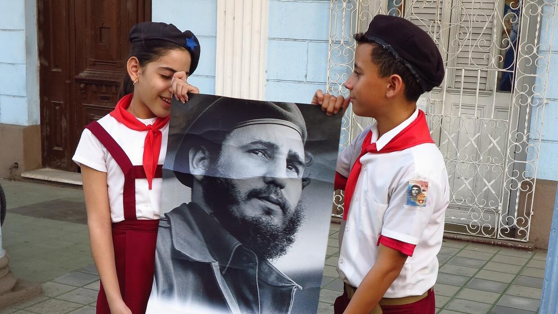 Dos pioneritos sostienen un retrado de Fidel joven en una calle de Cienf...