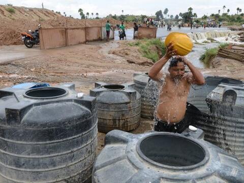 Un trabajador de la construcción en la India toma un baño...