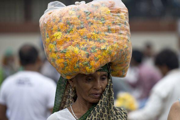 Esta mujer india carga una bolsa de flores en un mercado de flores al po...