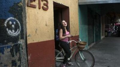 Una adolescente recorre las calles de Tepito en bicicleta.