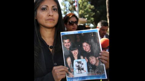 Claudia Osuna, abogada de la esposa acusada, sostiene foto de la familia...