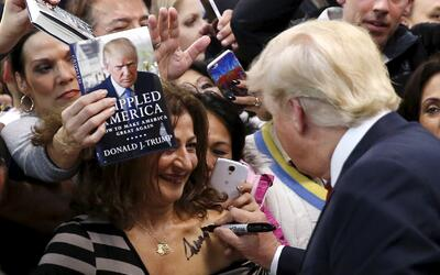 Donald Trump firma un autógrafo sobre el pecho de una mujer duran...
