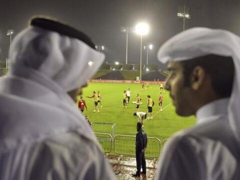 Dos hombres con vestimentas árabes presencian el entrenamiento de...