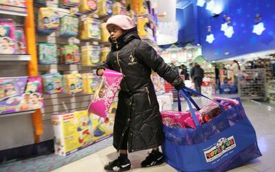 Una niña carga juguetes en Black Friday en una tienda de Nueva York