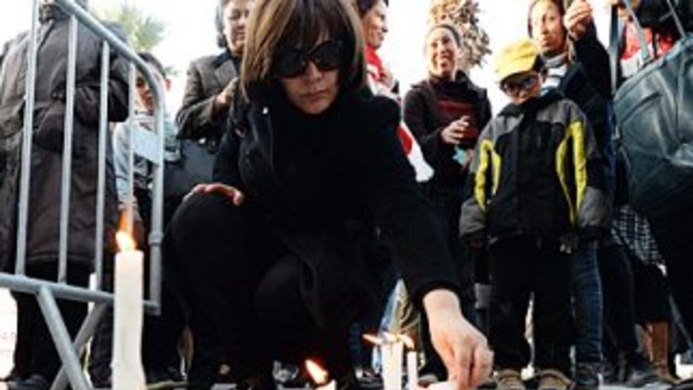 Una mujer enciende una vela en un altar erigido frente al Museo Nacional...