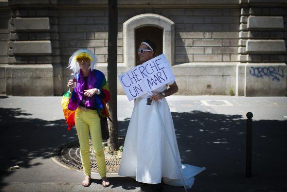 """Un hombre sostiene un cártel que dice """"En busca de un marido"""" en Francia."""