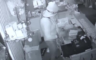 Un hombre entra a robar a una tienda de artículos de baile vestido con m...