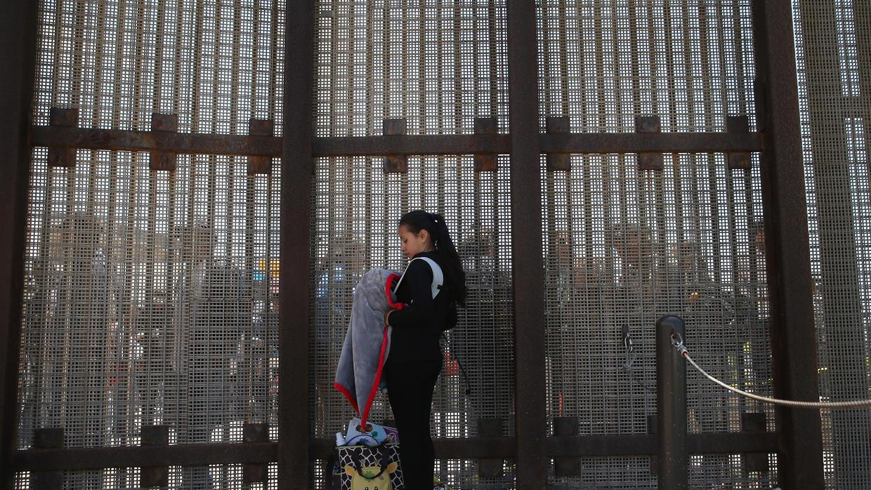 Karen Herrera, 23, and her infant son Ivan, on the border in San Diego,...