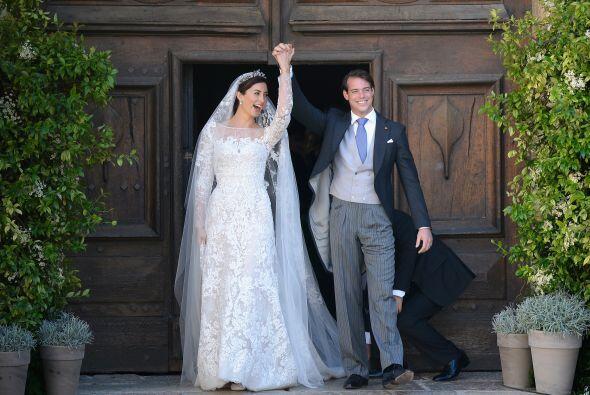 El nuevo matrimonio real levantó sus brazos con sus manos entrela...