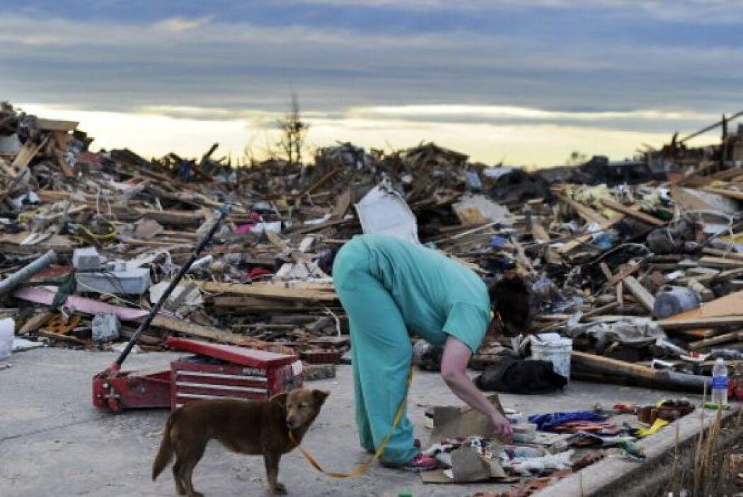 Los sobrevivientes al tornado recuperan sus recuerdos entre los escombros.