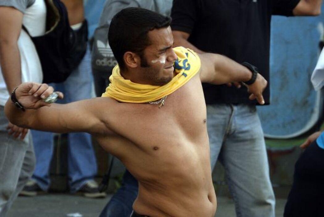 Un joven lanaza piedras contra un grupo de policias que tratan de disper...