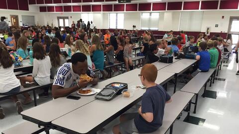 El jugador Travis Rudolph y el niño Bo Paske almuerzan en una cafetería...
