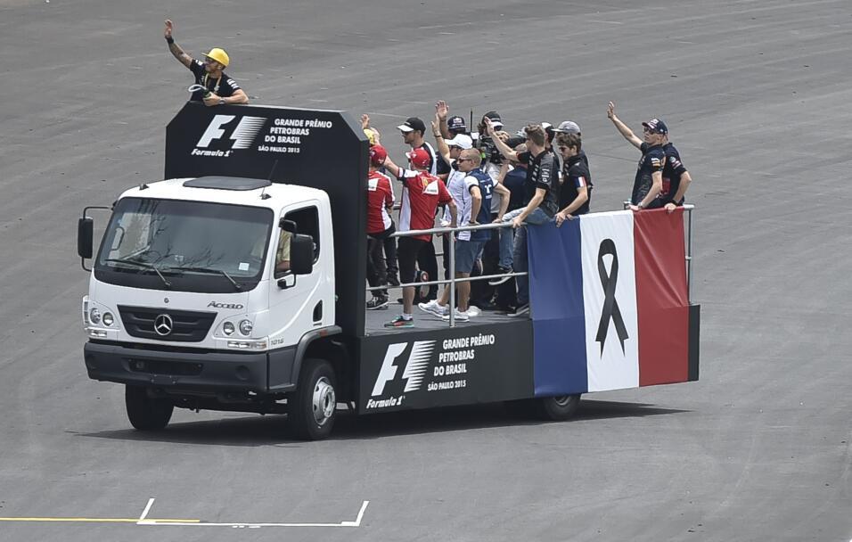 Corredores de Formula 1 desfilan a bordo de un camión con una bandera fr...