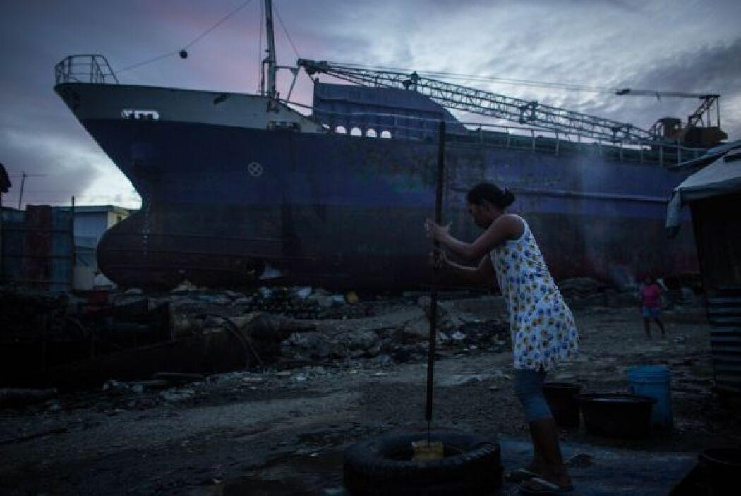 Una mujer saca agua de un improvisado bien en la zona costera de Tacloba...