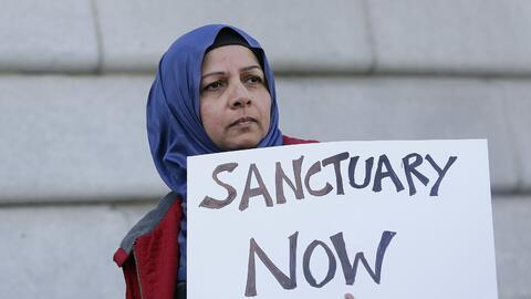 Una mujer en San Francisco se manifiesta a favor de las políticas...