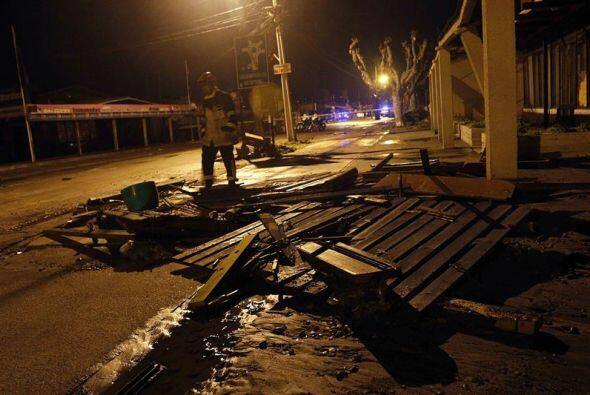 Un hombre pasa al lado de varios destrozos causados una ola.