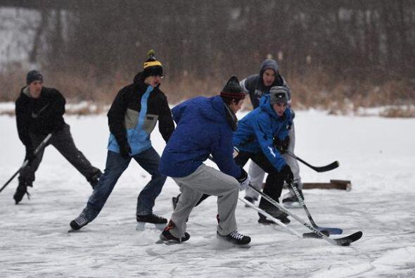 Un grupo de jóvenes de Wrentham y Norfolk juegan hockey, mientras cae ni...