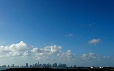 Entre nubes gigantes, un cielo azul cubre una línea de edificios de lujo...