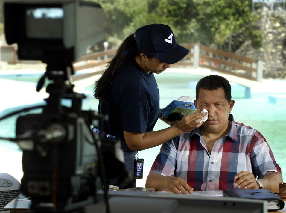 An assistant wipes Venezuelan President Hugo Chavez's face during hi...