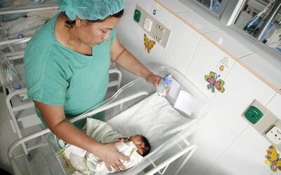 Una enfermera atiende un bebé con microcefalia, una malformaci&oa...